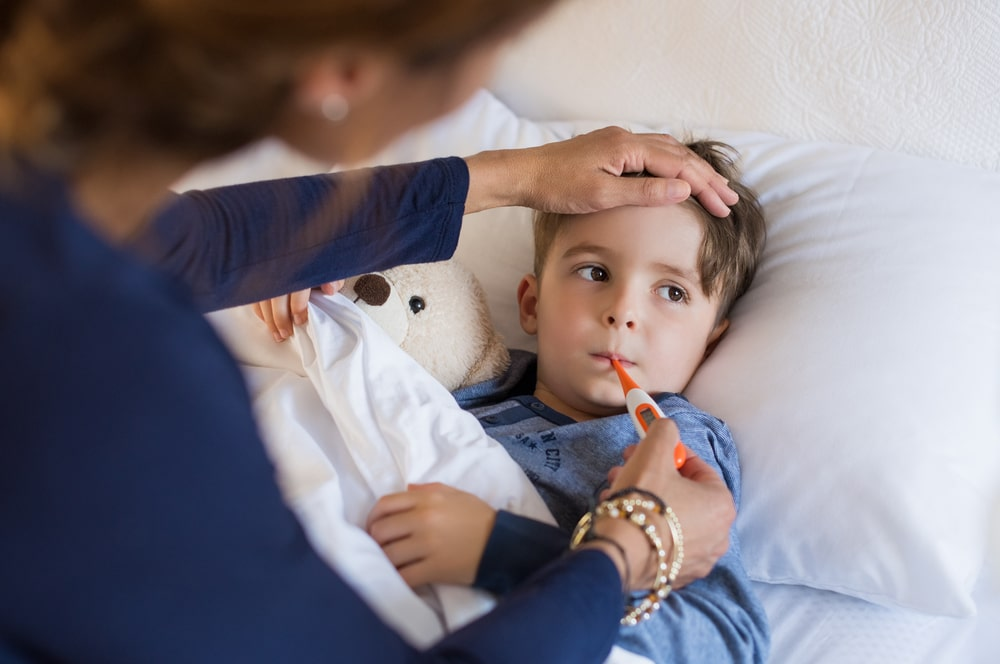beneficios da vitamina a menino deitado na cama com febre