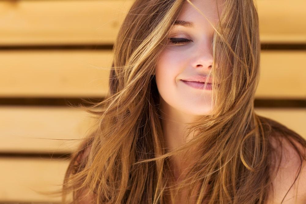 beneficios da vitamina a mulher sorrindo cabelos castanhos